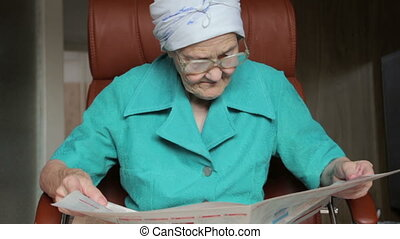 old woman reading newspaper - old woman sitting on chair and...