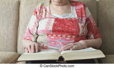 Old woman reading the book on the couch