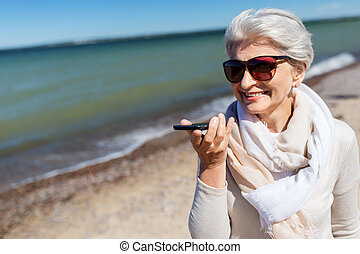 old woman recording voice by smartphone on beach