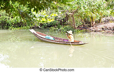 Old woman rowing a wooden on the river