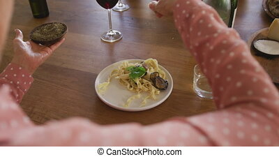 Over the shoulder view of a senior adult Caucasian woman sitting at a table relaxing with her colleagues after a cookery class in a restaurant kitchen, seasoning a dish of freshly cooked pasta they have prepared together, in slow motion