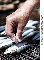 old woman salting some sardines in a grill - closeup of an...