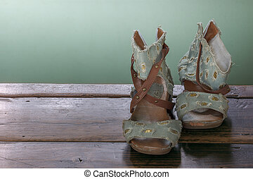 Old woman shoes on grunge wooden background.