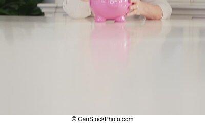 Old woman showing piggybank