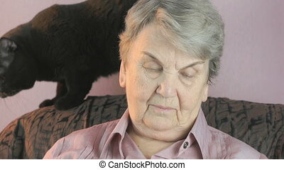 Old woman sits at a armchair next to a black cat - Old woman...