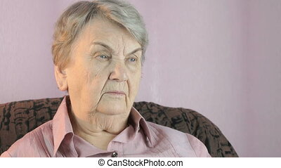 Old woman sitting indoors covers face her hands - The old...