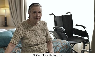 Old woman sitting on the bed next to the wheelchair