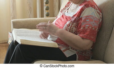 Old woman sitting on the sofa reading a thick book