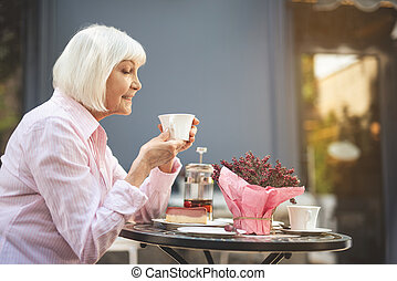 Old woman sitting outside and drinking tea