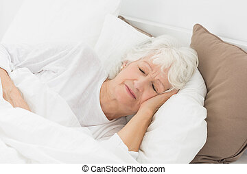 Old woman sleeping on the bed
