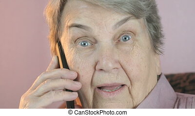 Old woman smiling talks on mobile phone. Close up