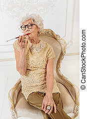 Old woman smoking cigarette at home