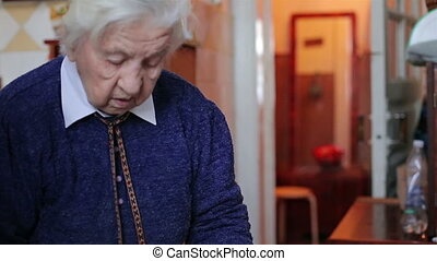 Old woman spreading butter on a piece of bread