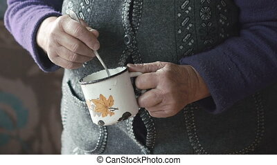 Old woman stiring eggs in the metal mug with shaked hands