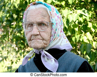 Old woman - Old grey woman with headscarf against green...