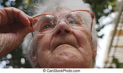 Old woman straightens her glasses and looking forward....