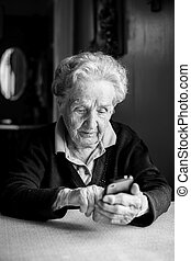 Old woman takes on smartphone sitting at the table in the house. Black-and-white photo.