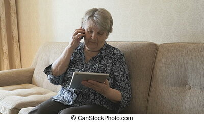 Old woman talking a mobile phone sitting on a sofa