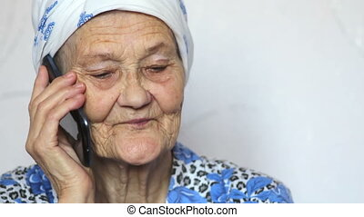 old woman talking on smartphone - portrait of old woman...