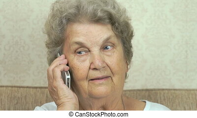 Old woman talking smartphone at home