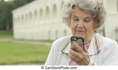 Old woman talking with a friend using a smartphone - Mature...