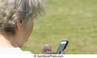 Old woman talking with relatives using smart phone