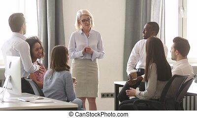 Old woman teacher coach training multicultural interns group...