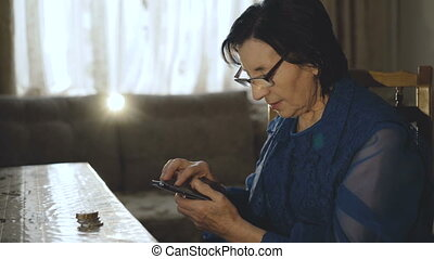 Old woman uses her bitcoin purse on the smartphone