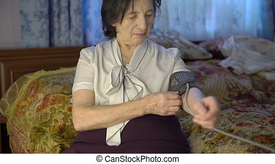 Old woman using blood pressure measurement tool on hand with electronic screen
