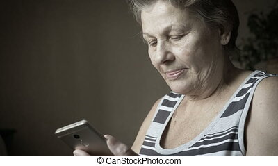 Old woman using new smartphone. - Smiling senior woman using...