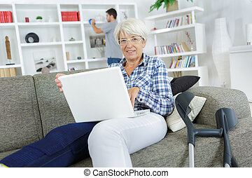 old woman using the laptop while sitting on the sofa