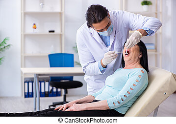 Old woman visiting young doctor dentist