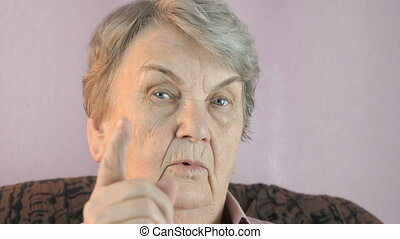 Old woman waves her index finger in front of face