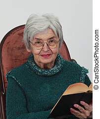 Portrait of an old woman with a black book against a grey background.