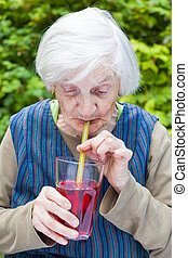 Old woman with alzheimer disease drinking raspberry juice