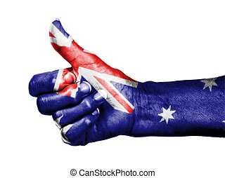 Old woman with arthritis giving the thumbs up sign, wrapped in flag pattern, Australia