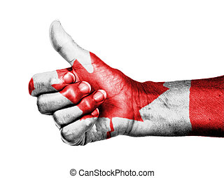 Old woman with arthritis giving the thumbs up sign, wrapped in flag pattern, Canada
