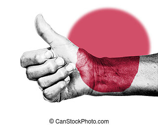 Old woman with arthritis giving the thumbs up sign, wrapped in flag pattern, Japan