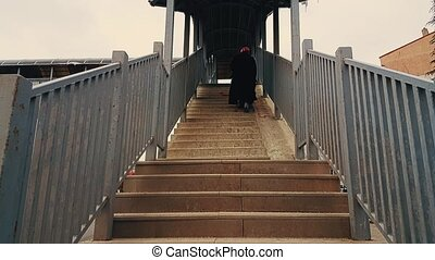 Old woman with black coat and hijab walking up the stairs of...
