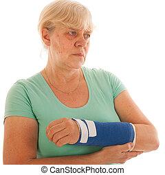 Old woman with broken wrist in gypsum