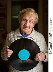 Old woman with disc in her hand