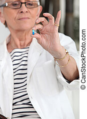 Old woman with drug in hand