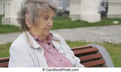 Old woman with gray hair sits on a bench outdoors