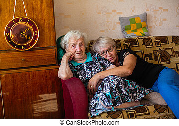 Old woman with her adult daughter sitting on the couch.