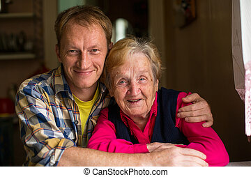 old woman with his adult grandson - Portrait of old woman...