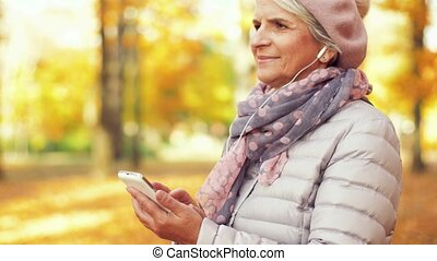 old woman with smartphone and earphones in autumn -...