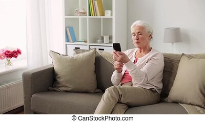 old woman with smartphone having video chat