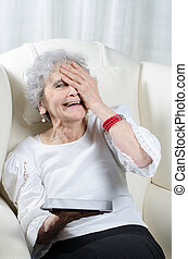 old woman with tablet in her hand laughing