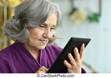 Old woman with tablet pc - Portrait of Old woman with tablet...