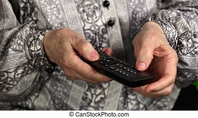 Old woman with tv remote control